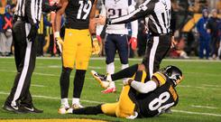 Pittsburgh Steelers wide receiver JuJu Smith-Schuster (19) looks on as wide receiver Antonio Brown (84) grabs his leg after suffering an apparent injury against the New England Patriots during the second quarter at Heinz Field. Photo: Charles LeClaire-USA TODAY Sports