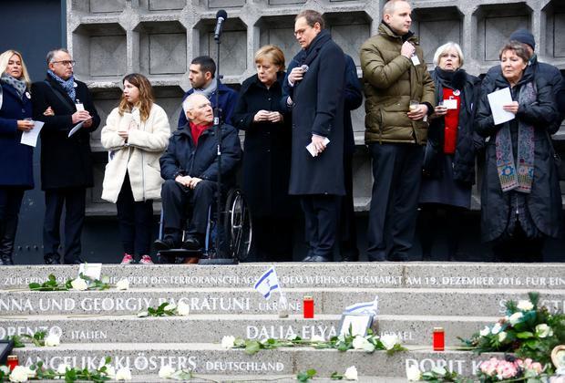 German Chancellor Angela Merkel and Berlin's Mayor Michael Mueller attend a ceremony at Breitscheidplatz square for the one year anniversary of a truck attack that killed 12 people and injured many others