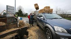 Stocking up on fodder outside the Drumshanbo Horse Fair, Co Leitrim. Jay Mulligan doing a good trade in square bales loads up a customer. Photo Brian Farrell