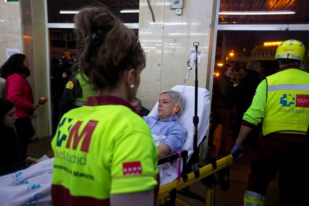 An injured passenger is taken from a train station to an ambulance in Alcala de Henares, central Spain, Friday, Dec. 22, 2017. Emergency services in Spain said more than 40 people were treated, four of them for serious injuries, after a double-decker commuter train crashed into a barrier in a town near Madrid on Friday. (AP Photo/Paul White)