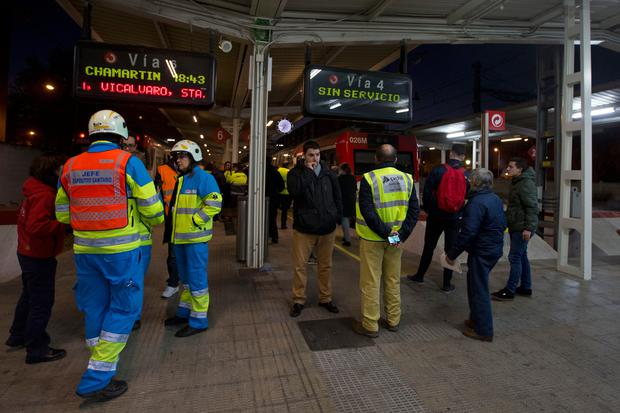 Emergency services stand near a train that hit the buffers in Alcala de Henares, central Spain, Friday, Dec. 22, 2017. Emergency services in Spain said more than 40 people were treated, four of them for serious injuries, after a double-decker commuter train crashed into a barrier in a town near Madrid on Friday. (AP Photo/Paul White)