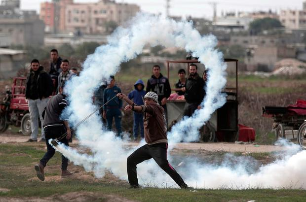 A Palestinian protester slings a teargas canister towards Israeli soldiers during clashes on the Israeli border with Gaza yesterday. Photo: Khalil Hamra/PA