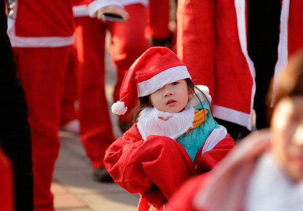 A girl dressed as a Santa Claus attends warm up training before a fun run ahead of Christmas Eve at Chaoyang park in Beijing, China December 23, 2017. REUTERS/Jason Lee