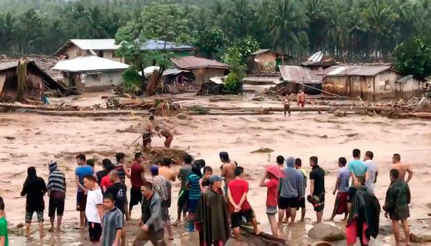 In this photo made from video by Aclimah Disumala, Friday, Dec. 22, 2017, villagers carry cross raging flood waters in Lanao del Norte, Zamboanga Pennisula, southern Philippines. (Aclimah Disumala via the AP)