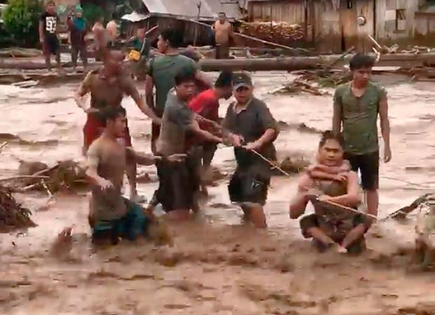In this photo made from video by Aclimah Disumala, Friday, Dec. 22, 2017, villagers cross raging flood waters in Lanao del Norte, Zamboanga Pennisula, southern Philippines. (Aclimah Disumala via the AP)