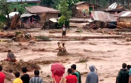 In this photo made from video by Aclimah Disumala, Friday, Dec. 22, 2017, villagers ross raging flood waters in Lanao del Norte, Zamboanga Pennisula, southern Philippines. (Aclimah Disumala via the AP)