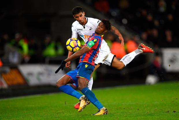 Wilfried Zaha of Crystal Palace is challenged by Kyle Naughton of Swansea City. Photo: Getty Images