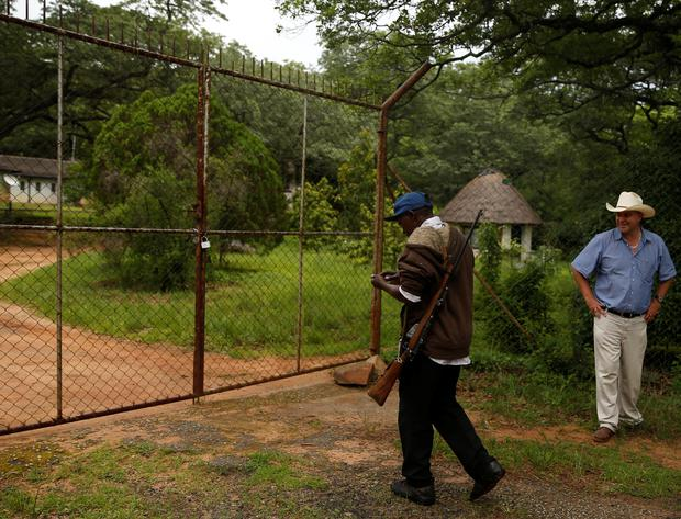 Commercial farmer Darreyn Smart looks on as private secuty gaurd unlocks the gate to his farm house at Lesbury Estates in Headlands communal lands east of the capital Harare,Zimbabwe, December 21, 2017. REUTERS/Philimon Bulawayo