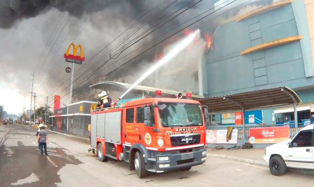 Firefighters extinguish a fire at a shopping mall in Davao City, the Philippines, in this December 23, 2017 photo obtained from social media. Courtesy of Tristan Ainin /via REUTERS
