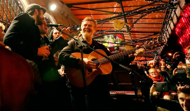 L-R Danny O'Reilly of the Coronas and Glen Hansard take part in the annual Christmas Eve busk in aid of the Dublin Simon Community outside the Gaiety Theater in Dublin. Photo: Niall Carson/PA Wire