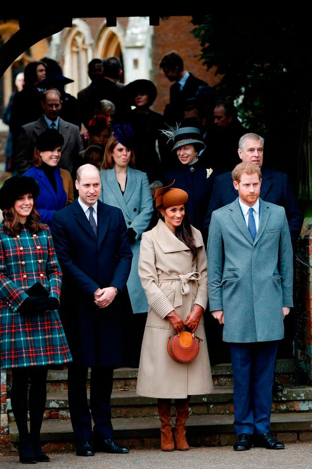 Britain's Catherine, Duchess of Cambridge, (L) and Britain's Prince William, Duke of Cambridge, (2L), US actress and fiancee of Britain's Prince Harry Meghan Markle (2R) and Britain's Prince Harry (R) stand together in front of other members of the family as they wait to see off Britain's Queen Elizabeth II after attending the Royal Family's traditional Christmas Day church service at St Mary Magdalene Church in Sandringham, Norfolk, eastern England, on December 25, 2017. / AFP PHOTO / Adrian DENNISADRIAN DENNIS/AFP/Getty Images