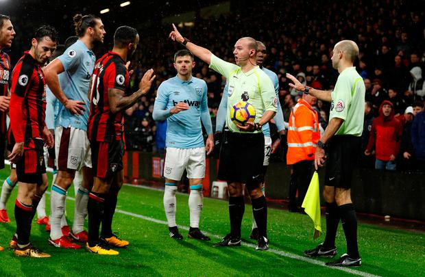 Players surround referee Robert Madley after he makes a decision regarding Bournemouth's late equaliser. Photo: REUTERS/Peter Nicholls