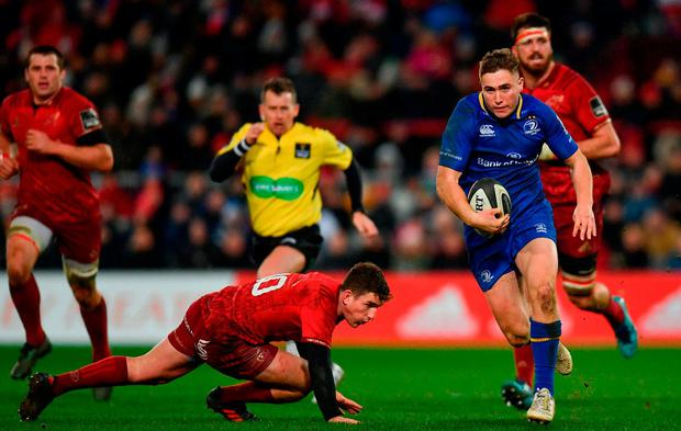 Jordan Larmour leaves Ian Keatley in his wake on his way to scoring a superb second-half try in Leinster's victory against Munster. Photo: RAMSEY CARDY/SPORTSFILE