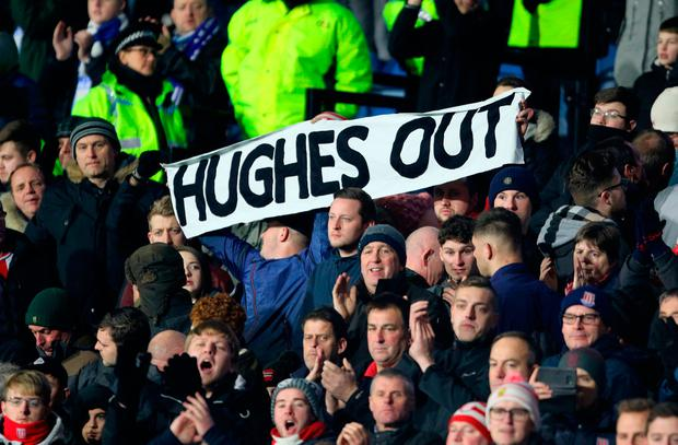 A Stoke City fan holds up a banner reading 'Hughes Out' at the John Smith's Stadium, Huddersfield. Photo: PA