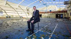 Jim Long, the principal of Douglas Community School in Cork, surveys the damage to the gym after Hurricane Ophelia ripped off the roof Photo: Mark Condren