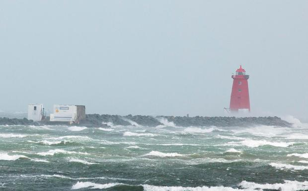 Waves break over the wall at the Poolbeg Lighthouse in Dublin Photo: Collins