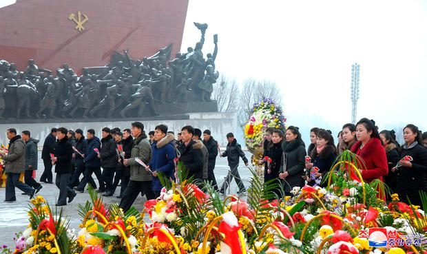 Workers and students place wreaths at the statutes of former North Korean leaders Kim Il-sung and Kim Jong-il. Photo: Reuters/KCNA