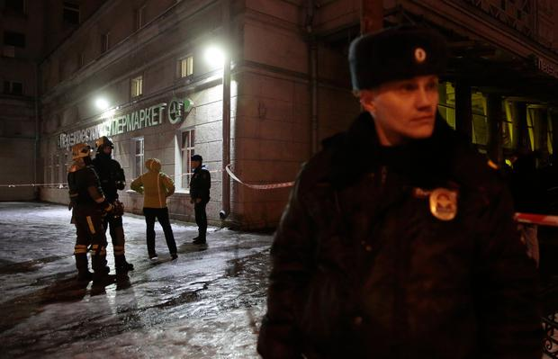 Emergency Ministry members and policemen are seen outside a supermarket after an explosion in St Petersburg