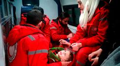 Red Cross workers evacuate a baby in Douma in the eastern Ghouta region of the Syrian capital Damascus. Photo: Reuters. Photo: Getty Images