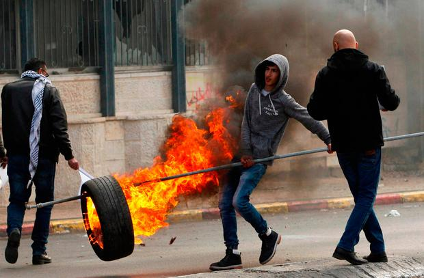 A Palestinian youth holds a burning tyre during clashes with Israeli forces. Photo: Getty Images