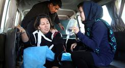People assist an injured woman following a suicide attack in Kabul, Afghanistan, Thursday, Dec. 28, 2017. Authorities say two simultaneous attacks in Afghanistan's capital have left dozens dead. (AP Photo/Rahmat Gul)