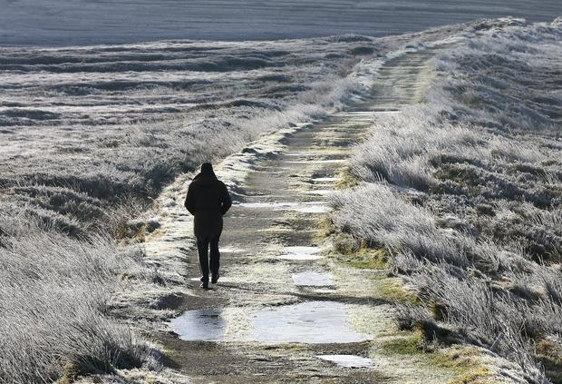 A walker strolls along a frozen boreen near Kippure, Co Wicklow. Picture Frank Mc Grath