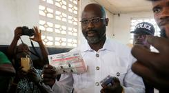 George Weah prepares his ballot during presidential elections at a polling station in Monrovia, Liberia