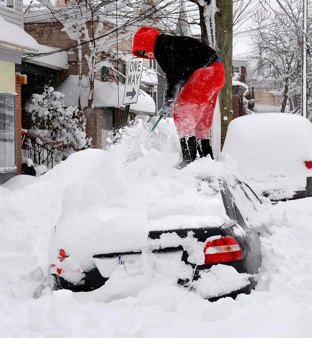 Soledda Hernandez stands on the roof of her car as she brushes off snow in Erie, Pennsylvania. Photo: Greg Wohlford/Erie Times-News via AP