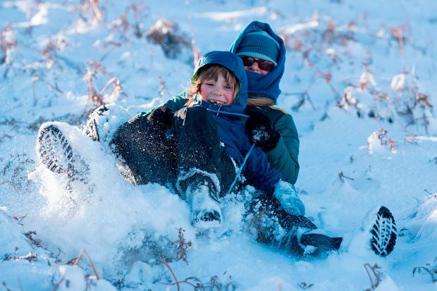 Josef Jackson (7) and Corieme Preston sledging on the Malvern Hills in Worcestershire. Photo: Aaron Chown/PA Wire