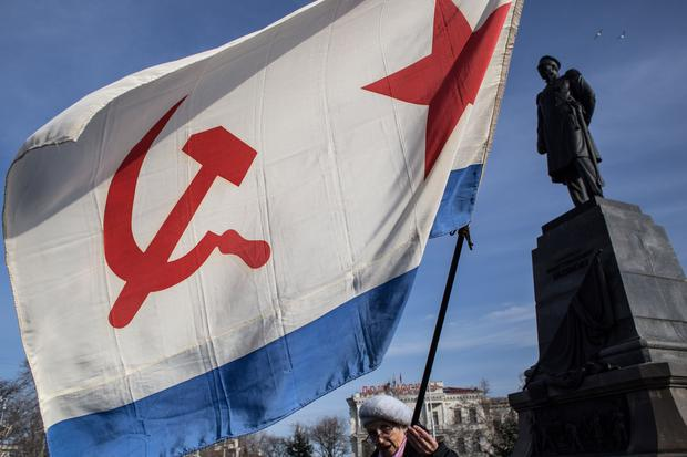 A woman holds the Flag of the Soviet Navy near the monument of admiral Pavel Nakhimov as Crimeans celebrate the first anniversary of the referendum on March 16, 2015 in Sevastopol, Crimea (Photo by Alexander Aksakov/Getty Images)