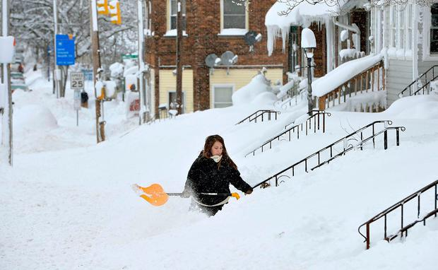 Rochelle Carlotti, 28, shovels steps near her home after a record snowfall in Erie, Pennsylvania. Monday's storm brought 34 inches of snow, an all-time daily snowfall record for Erie. Photo: AP