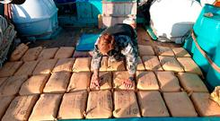 This handout taken on December 28, 2017 and released by the Australian Department of Defence on December 30, 2017 shows leading Seaman Clearance Diver Luke Woodcroft from the HMAS Warramunga numbering parcels of seized narcotics on the deck of a trafficking vessel at sea.