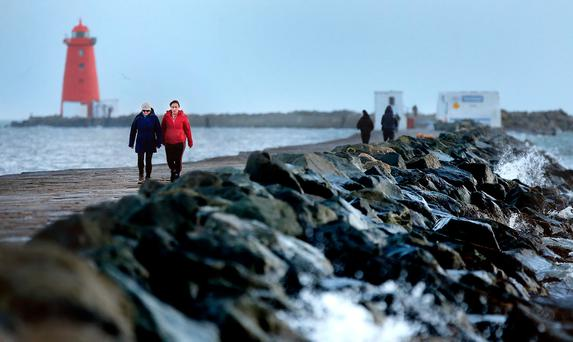 BEFORE THE STORM: Walkers on the Great South Wall in Dublin ahead of the arrival of Storm Dylan. Photo: Gerry Mooney