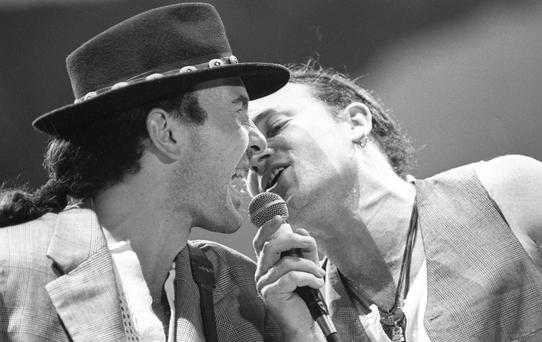 The Edge and Bono sharing the microphone during a song on stage at Croke Park, Dublin, in June 1987, during U2's The Joshua Tree Tour