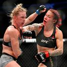 Cris Cyborg hits Holly Holm during a featherweight championship mixed martial arts bout at UFC 219