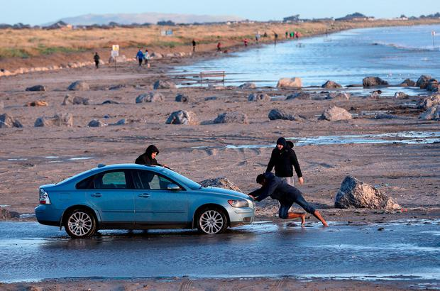 Men attempt to move a car on Dollymount Strand, Dublin. Photo: PA