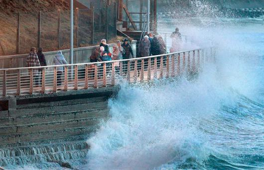 Raging waves swamp people walking the promenade area in Portrush, Co. Antrim as Storm Dylan gradually makes its way through the area. Photo: Margaret McLaughlin