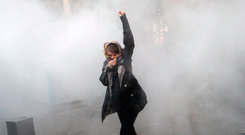 An Iranian woman raises her fist amid tear gas at the University of Tehran during a protest driven by anger over economic problems Photo: STR/AFP/Getty Images