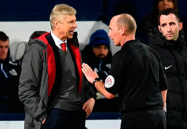 Arsene Wenger makes his views known to Mike Dean after the referee's decision to award a penalty to West Brom on Sunday Photo: Getty