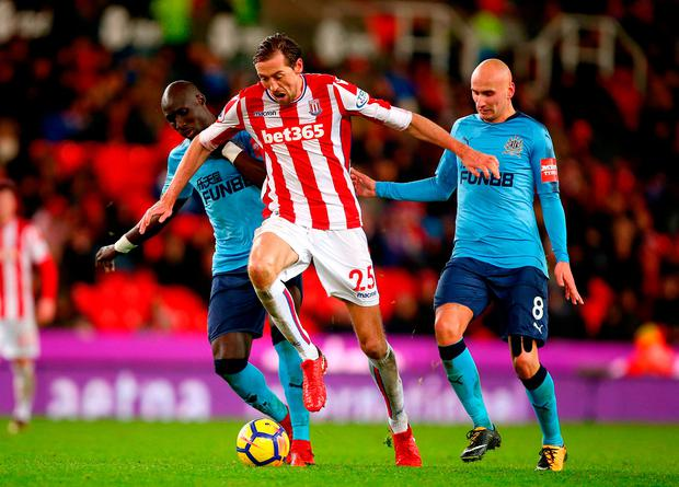 Stoke City's Peter Crouch (centre) battles for the ball with Newcastle United's Jonjo Shelvey (right) and Mohamed Diame (left). Photo credit: Dave Thompson/PA Wire