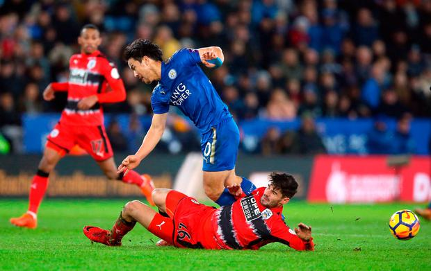 Leicester City's Shinji Okazaki and Huddersfield Town's Christopher Schindler (floor) battle for the ball. Photo credit: Nigel French/PA Wire