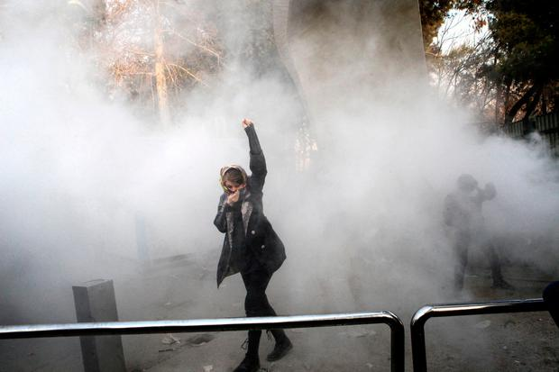 A university student attends a protest inside Tehran University while a smoke grenade is thrown by anti-riot Iranian police, in Tehran, Iran (AP Photo, File)