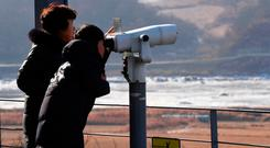 Visitors look through binoculars during a visit to the Imjingak peace park near the Demilitarised Zone (DMZ) dividing the two Koreas. Photo: Getty Images