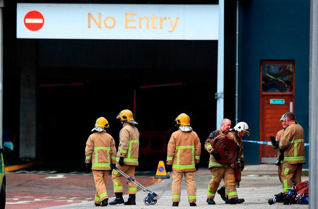 Firefighters at the scene the morning after the inferno. Photo credit: Peter Byrne/PA Wire