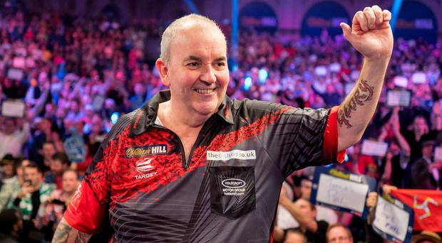 Phil Taylor gestures to his supporters after losing to Rob Cross at the PDC World Darts Championship 2018 final game in London. Photo: Tolga Akmen/AFP/Getty Images
