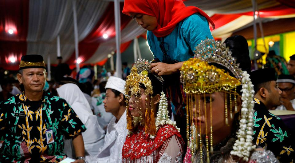 A bride has her headdress adjusted while taking part in a mass wedding organised by the city government as part of New Year's Eve celebrations in Jakarta, Indonesia, December 31, 2017. REUTERS/Darren Whiteside