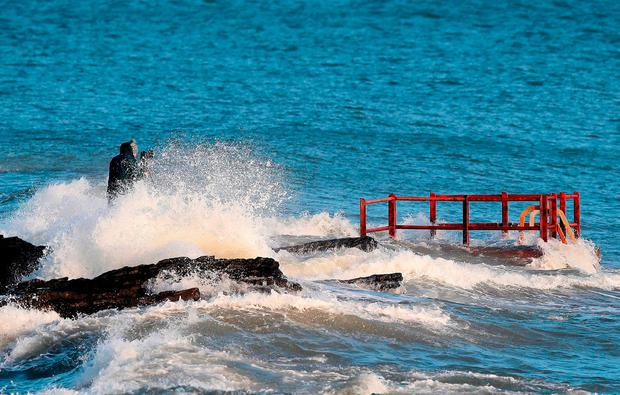 A man taking photographs gets caught by crashing waves at High Rock in Portmarnock, Dublin. Photo: Brian Lawless/PA