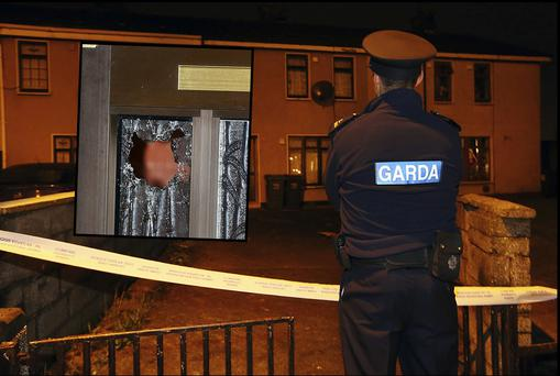 A garda pictured at the scene and inset, broken glass in the front door