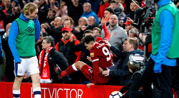 Liverpool's Roberto Firmino climbs out of the stands after being pushed by into them by Everton's Mason Holgate (not pictured). Action Images via Reuters/Carl Recine