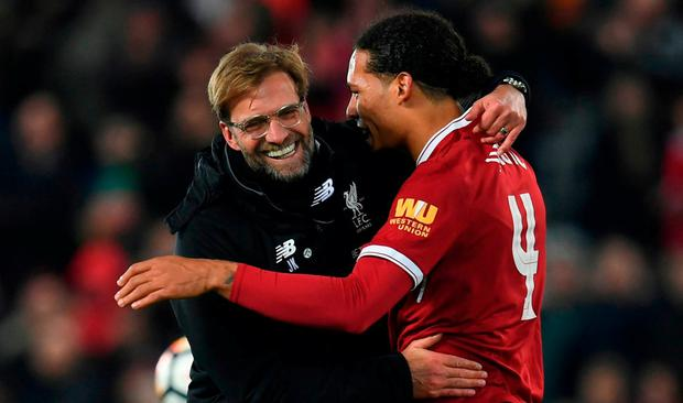 Liverpool's German manager Jurgen Klopp (L) hugs Liverpool's Dutch defender Virgil van Dijk (R) at the end of the English FA Cup third round football match between Liverpool and Everton at Anfield